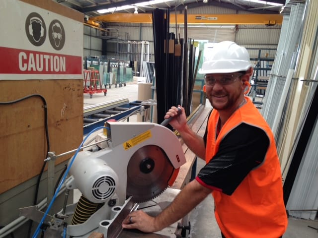 our expert team member cutting a steel panel part of a window